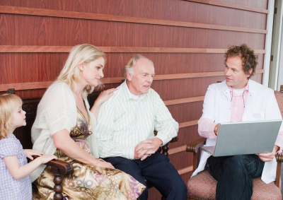 doctor showing his laptop to a senior man and his family